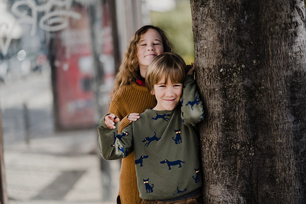 A boy and an slightly older girl stand beside a tree on a pavement.