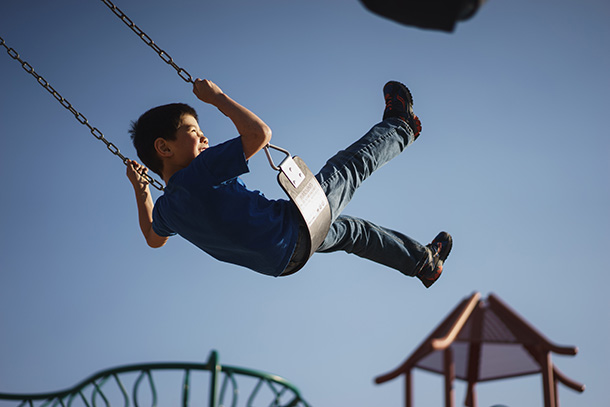 A boy on a swing sails high into the air